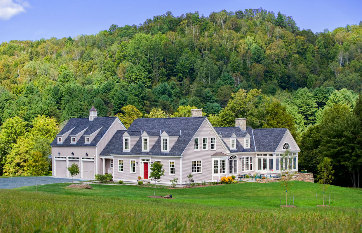 large gray house in the mountains in the summer