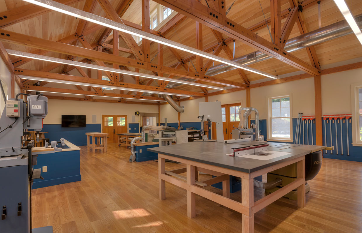 large wood shop with exposed ceiling framing