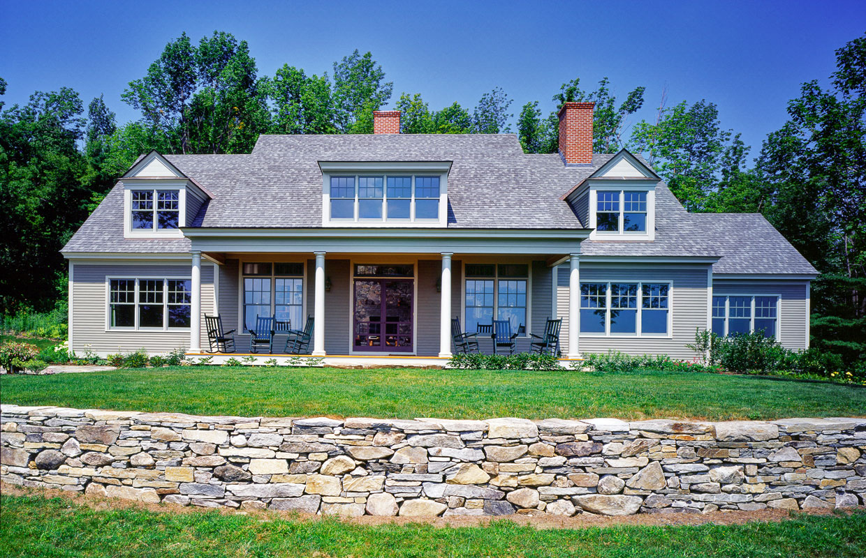 big gray house with a stone wall out front