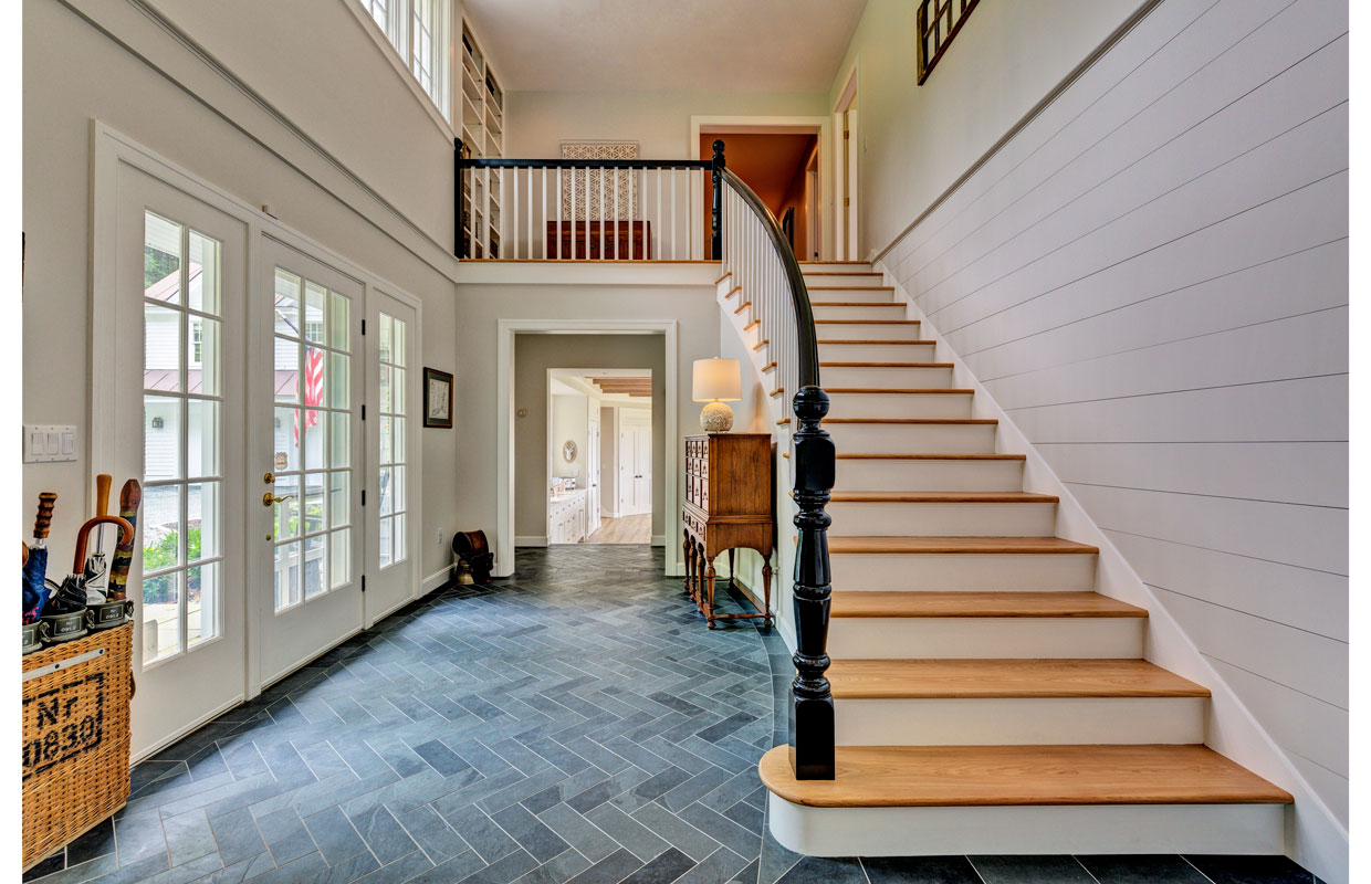 large staircase going up with a gray tile floor and open entryway below