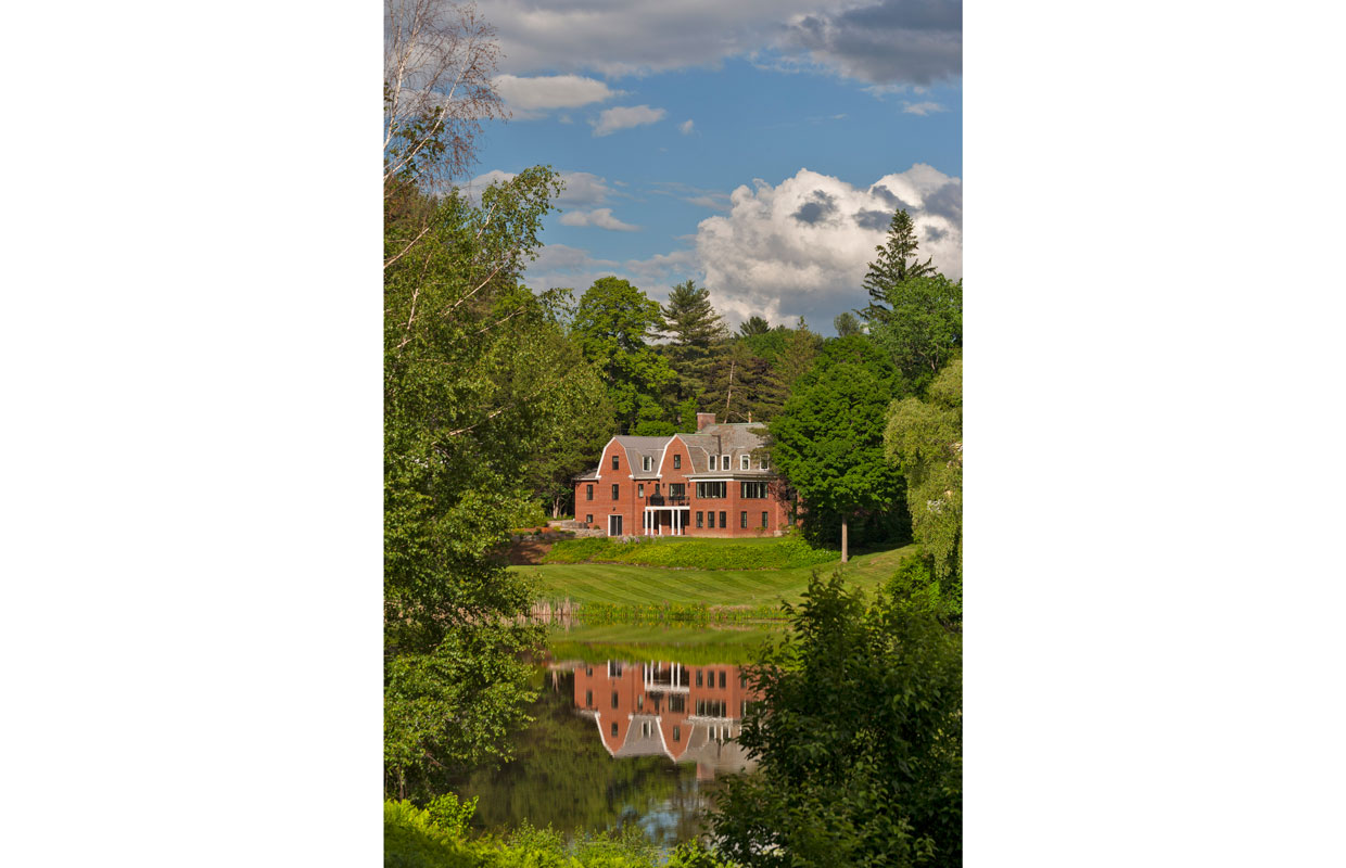 large brick house from a distance across a pond