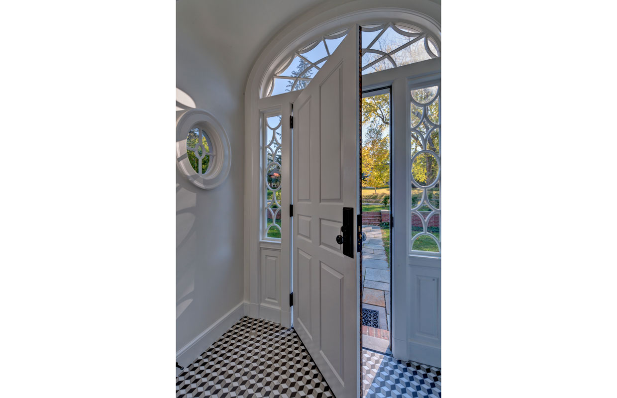 view from inside of a large white front door with black and white checker tile flooring