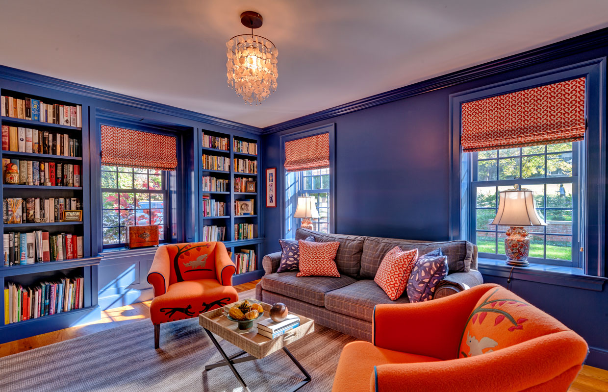 colorful reading room with orange furniture and bright blue walls