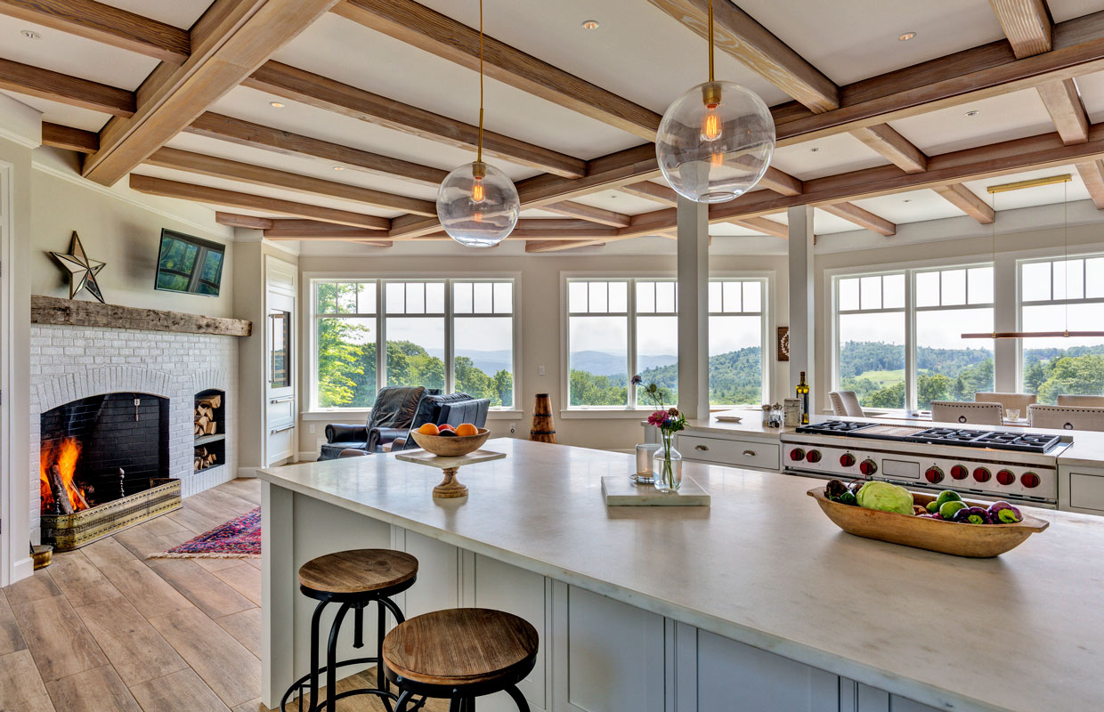 large kitchen with wrap around windows, exposed beams and a fireplace