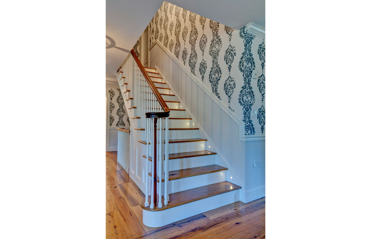 wooden stair case with blue and white wallpaper