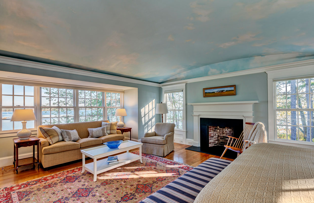 large living room with a fireplace and a blue sky scene painted on the ceiling