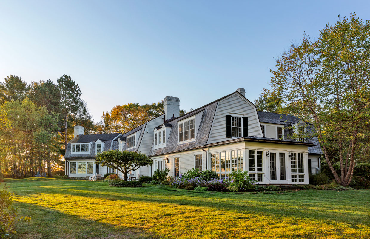 large gambrel white house with a black roof and a lush green yard