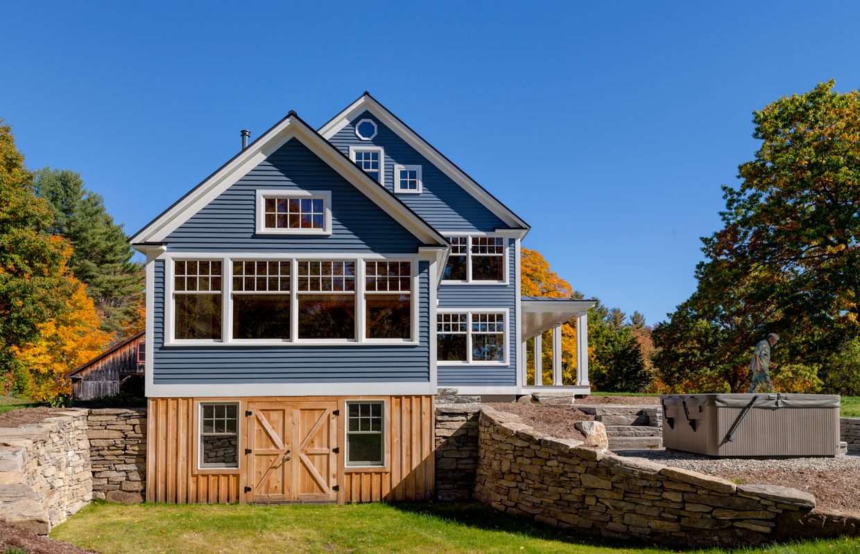 blue house with lots of windows and a wood-framed walk out basement and stonework