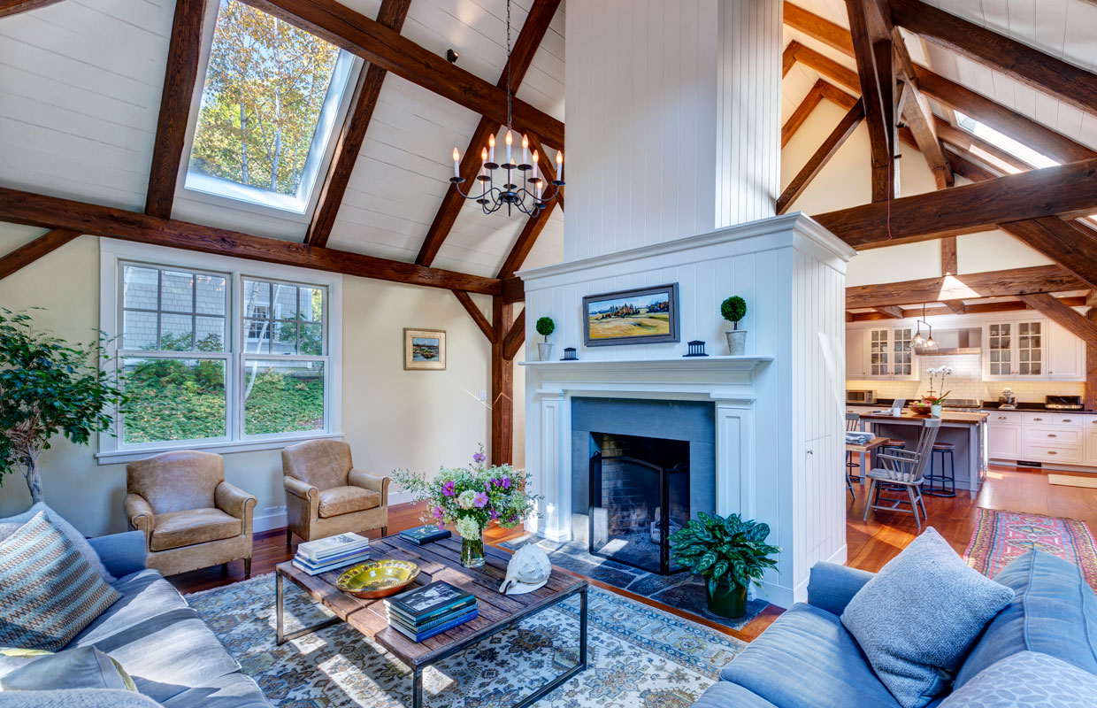 great room with white fireplace and exposed beams