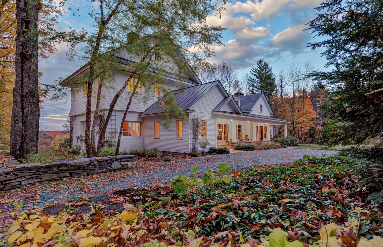 large white house in the fall with a stone driveway