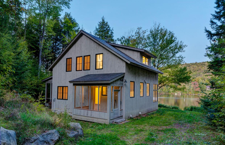 cottage at dusk with lights on inside