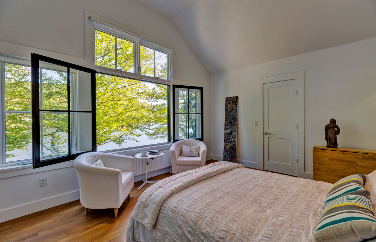 bedroom with large windows open to a lake view outside