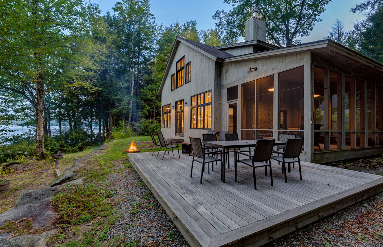 lakeside cottage at dusk with an outdoor fire pit and a deck