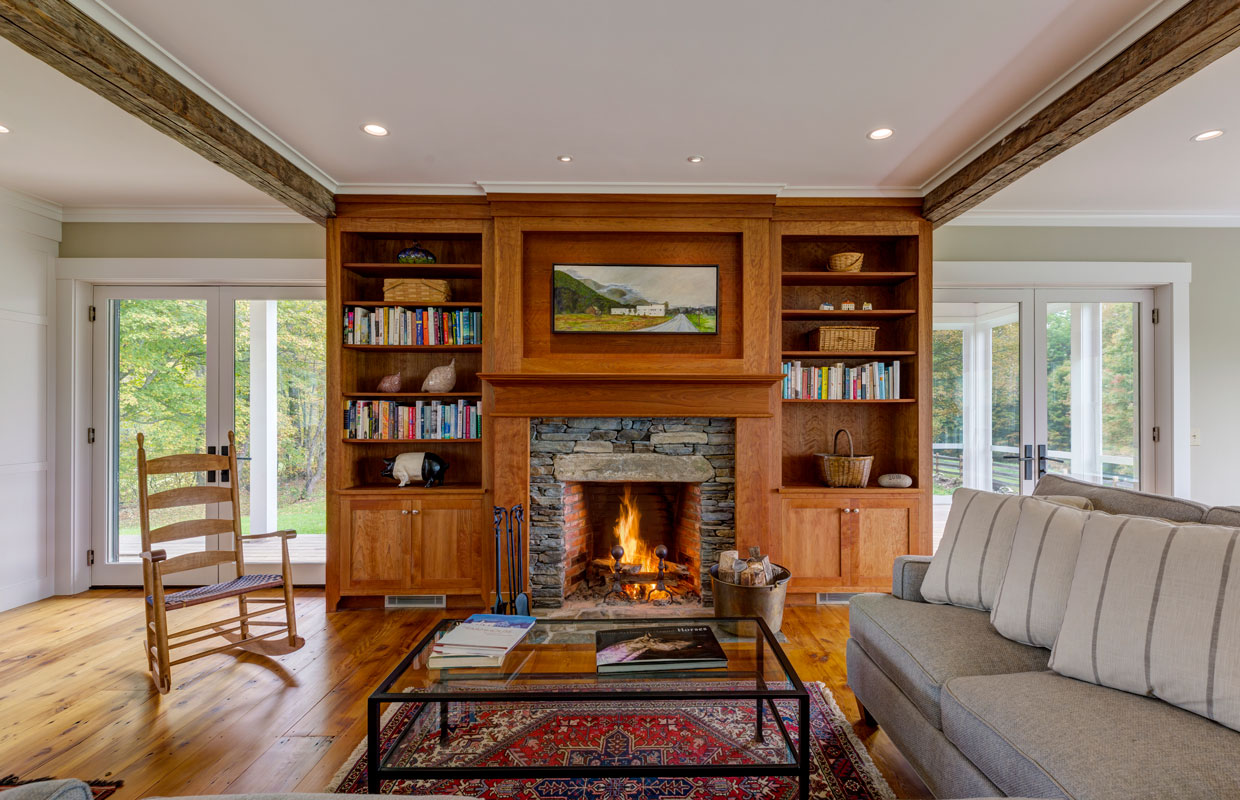 living room with a fireplace and surrounding bookcase
