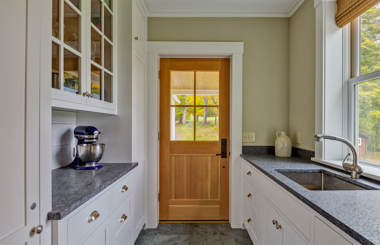wooden door with 4 window panes from the inside of a kitchen