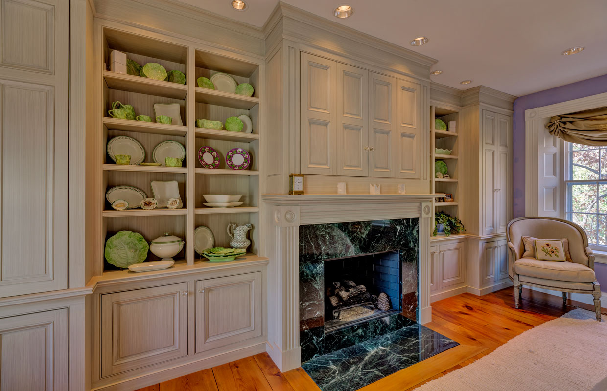 fireplace in a white built-in cabinet wall with green and white china