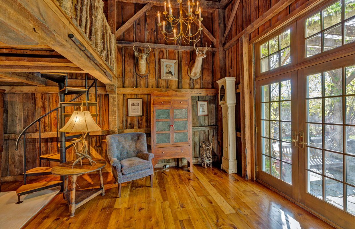 natural wood room with deer mounts on the wall and a spiral staircase