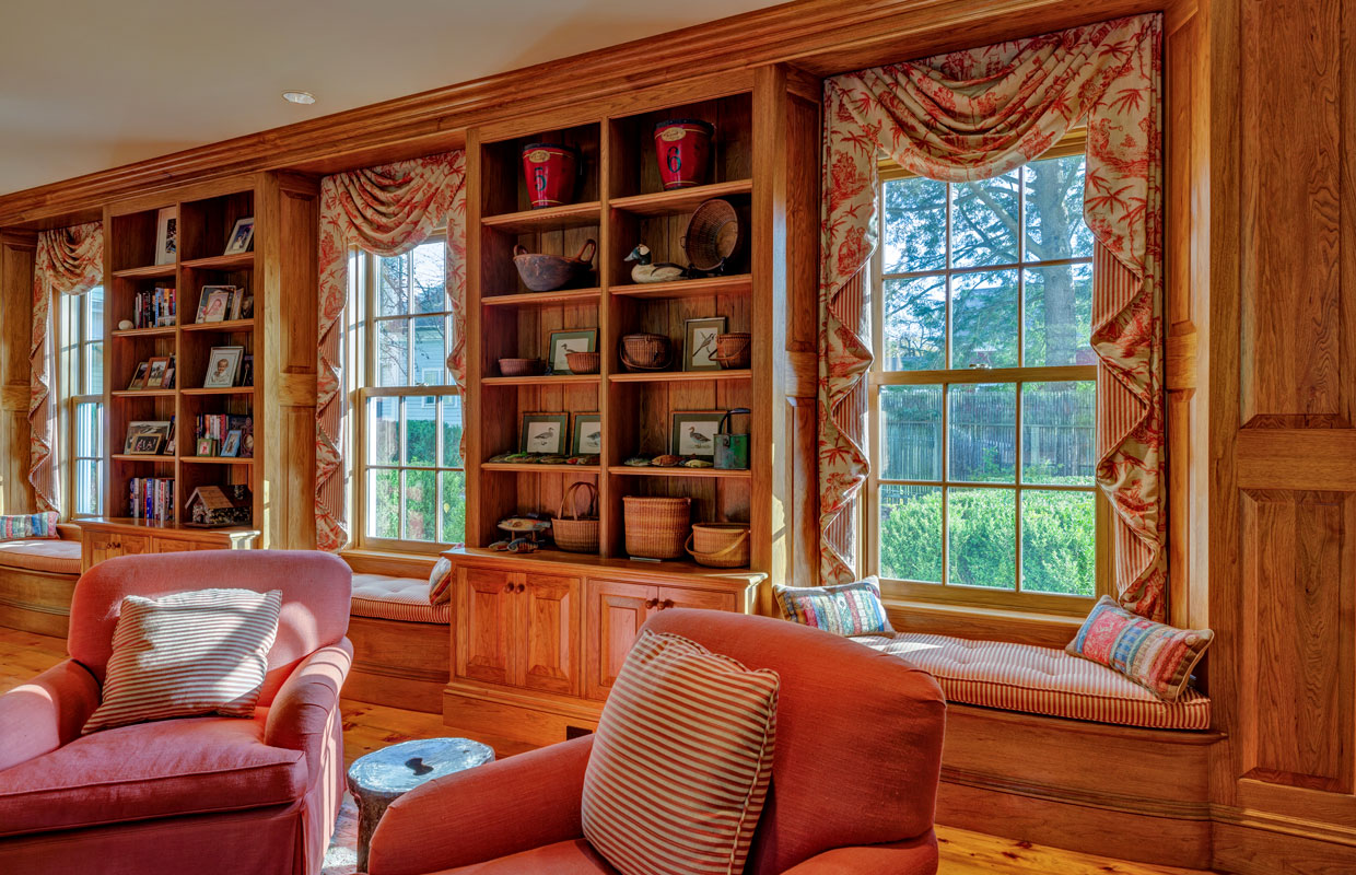 library in a home with fabric drapes over the windows