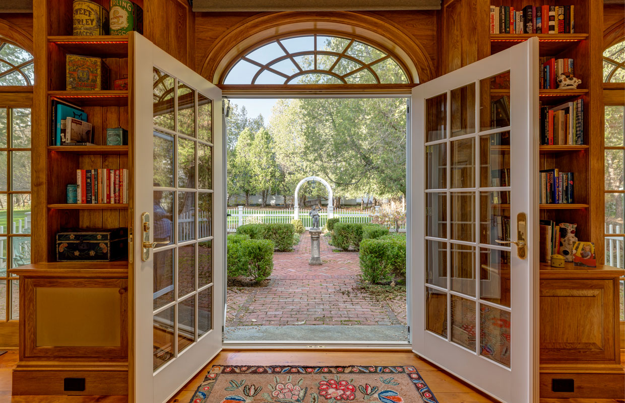 view of a garden from inside large open french doors with window panes