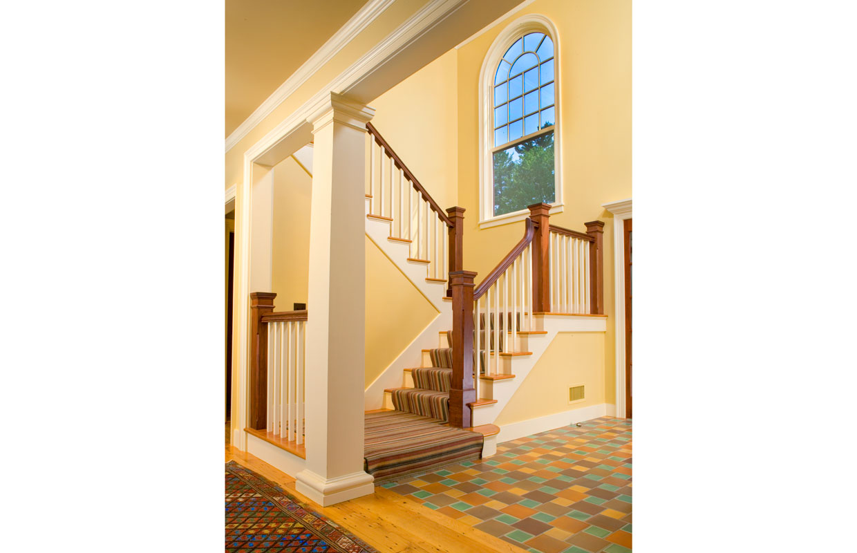 large yellow staircase with a colorful tile floor
