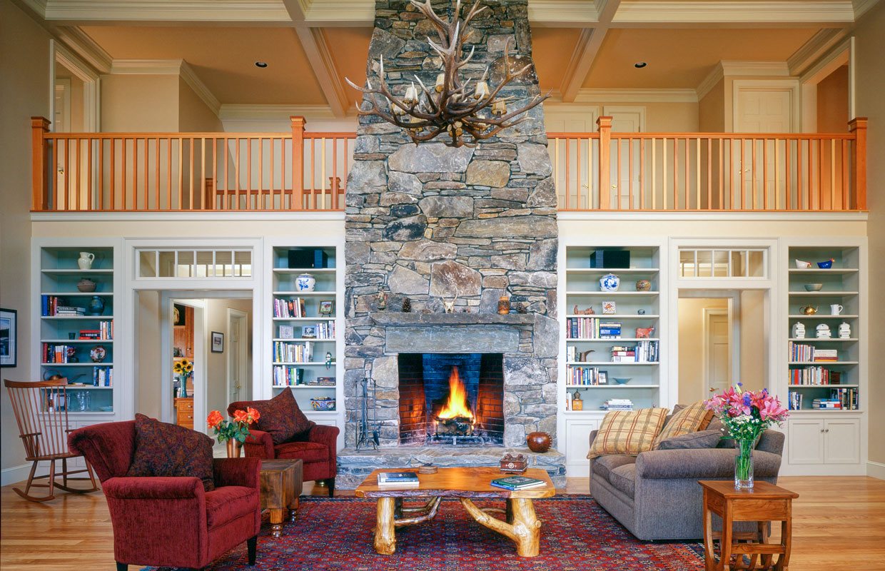 great room with a large fireplace and stone chimney in the center and a balcony behind