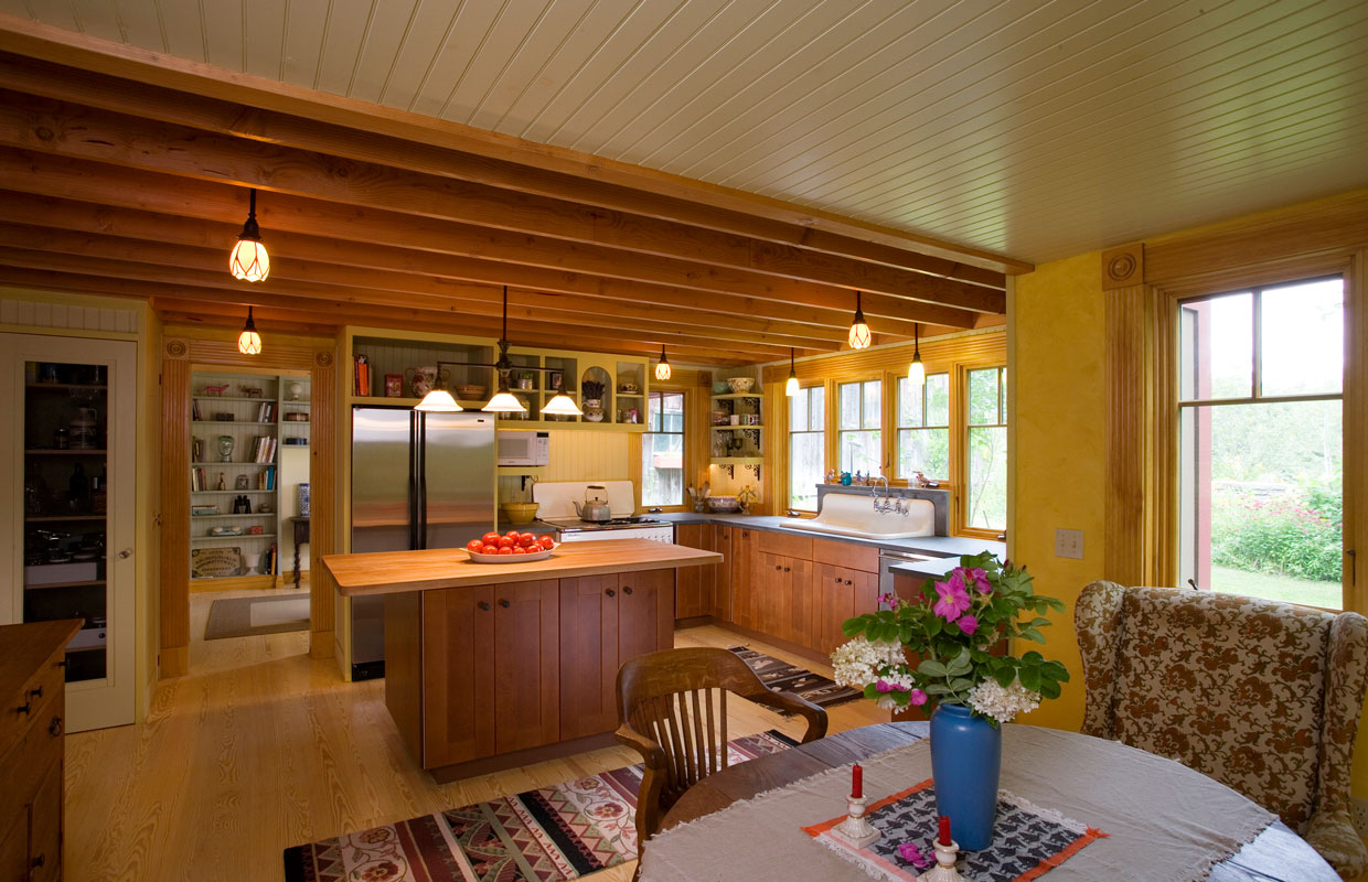 view into a kitchen from the dining room with lots of wood accents and natural light