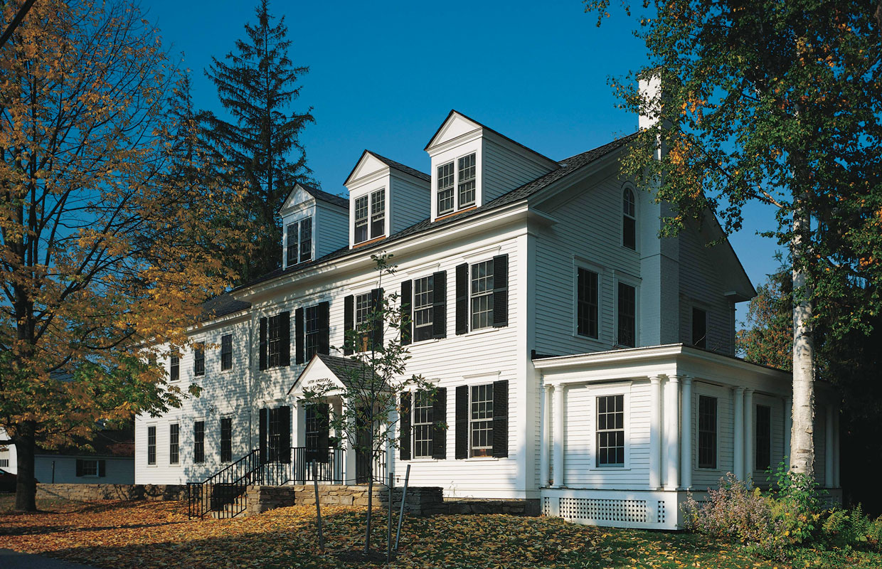large white colonial house in the fall
