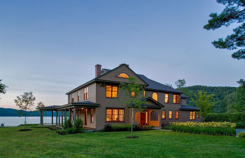 large lake house at dusk with lights on inside