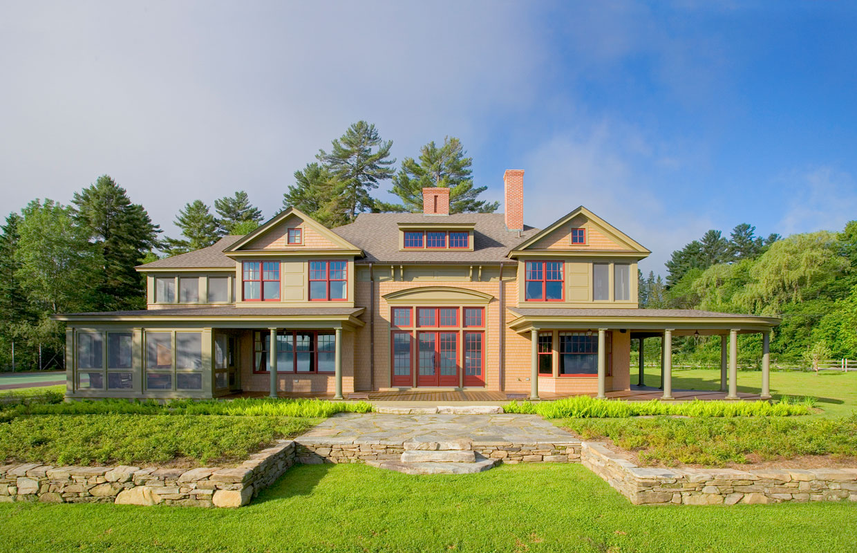 large tan house with red trim and stone work out front