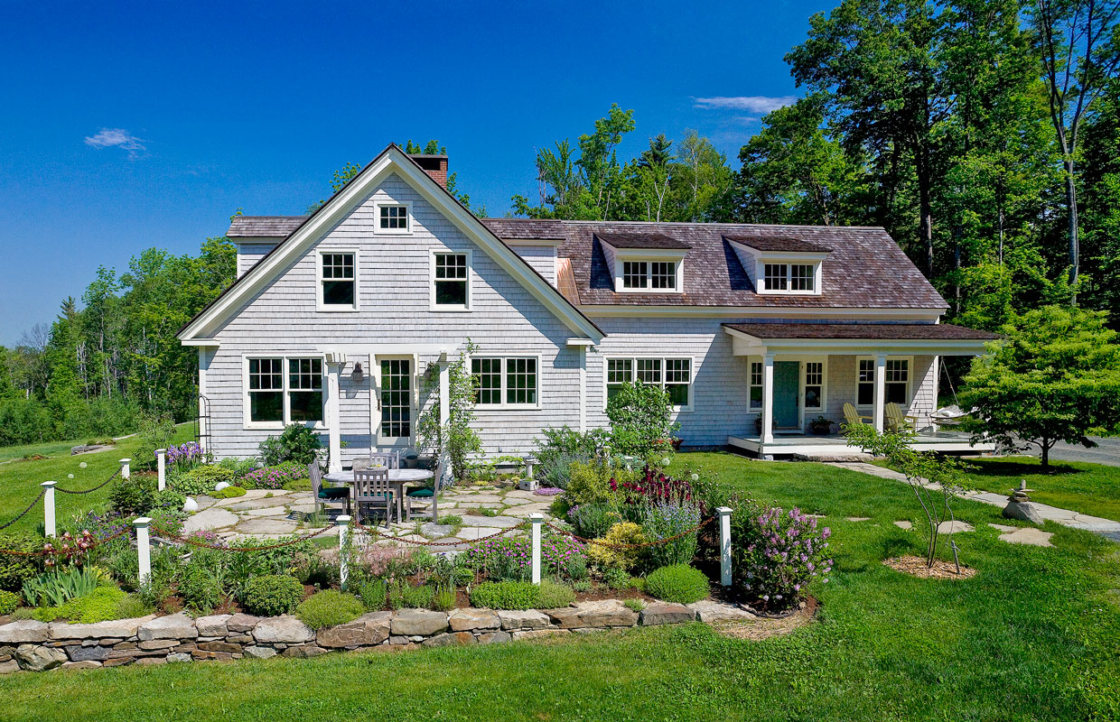 gray house with lush green lawn