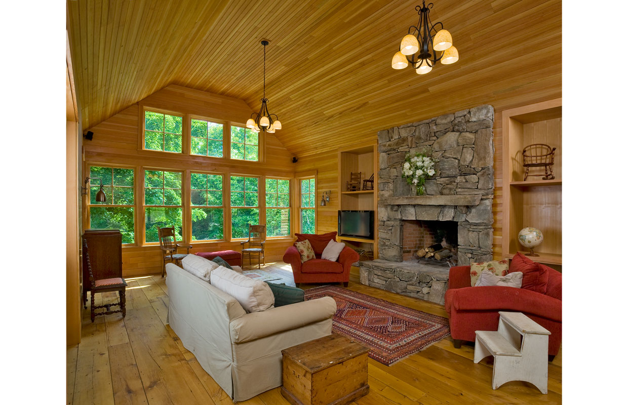 great room with a field stone fireplace and large windows