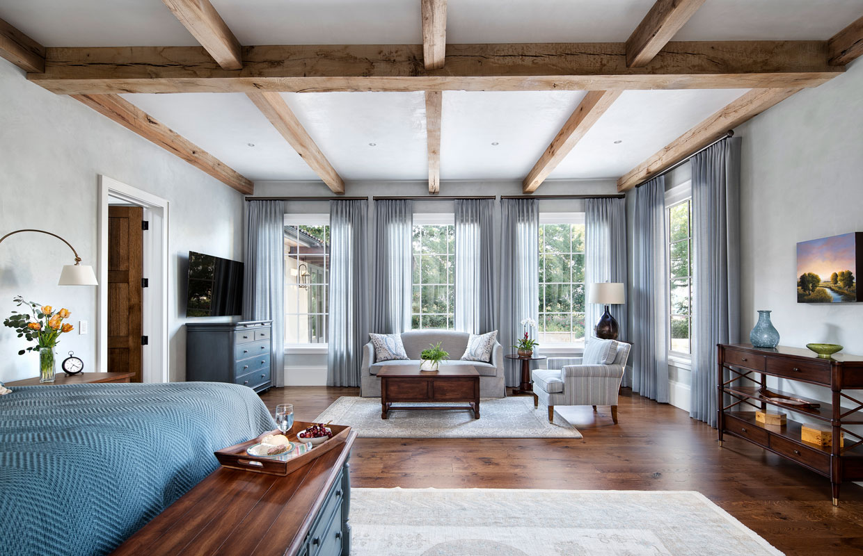 bedroom with exposed beams and large seating area
