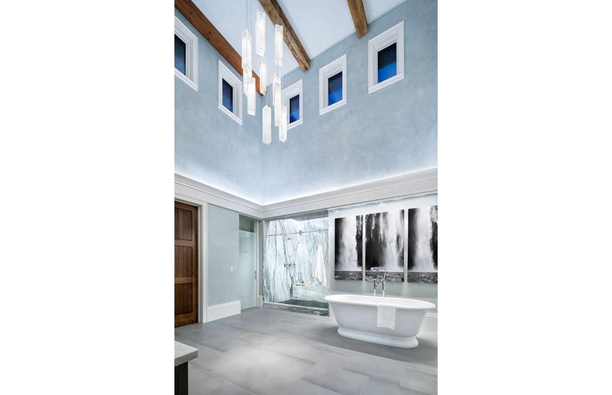 cathedral ceiling bathroom with marble shower and large bathtub