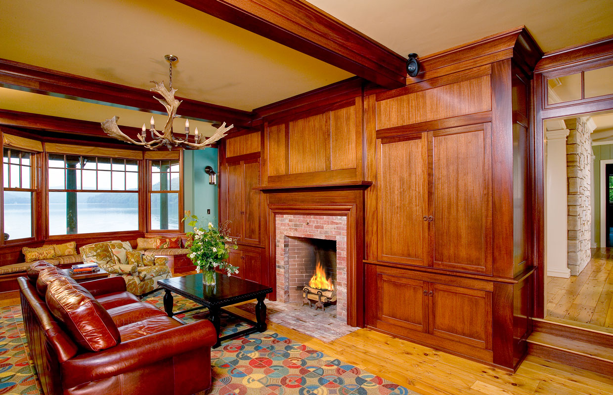 room with lots of wood accent and a fireplace and leather couch