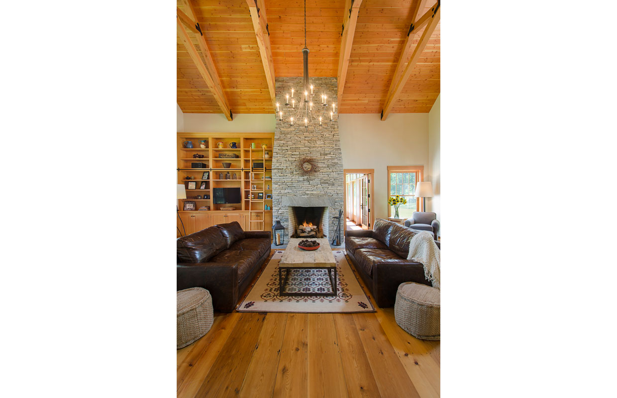 great room with wood ceilings and a stone fireplace