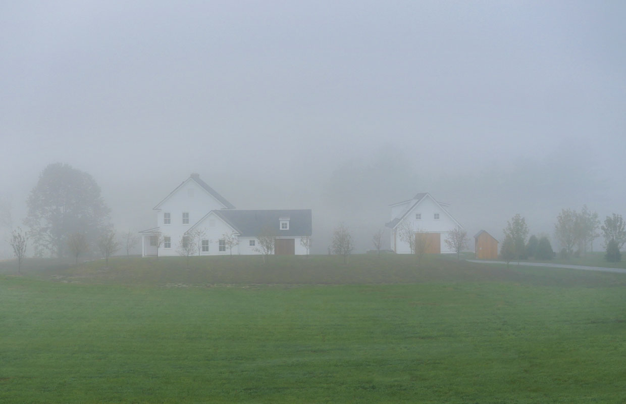 white farmhouse in a foggy field