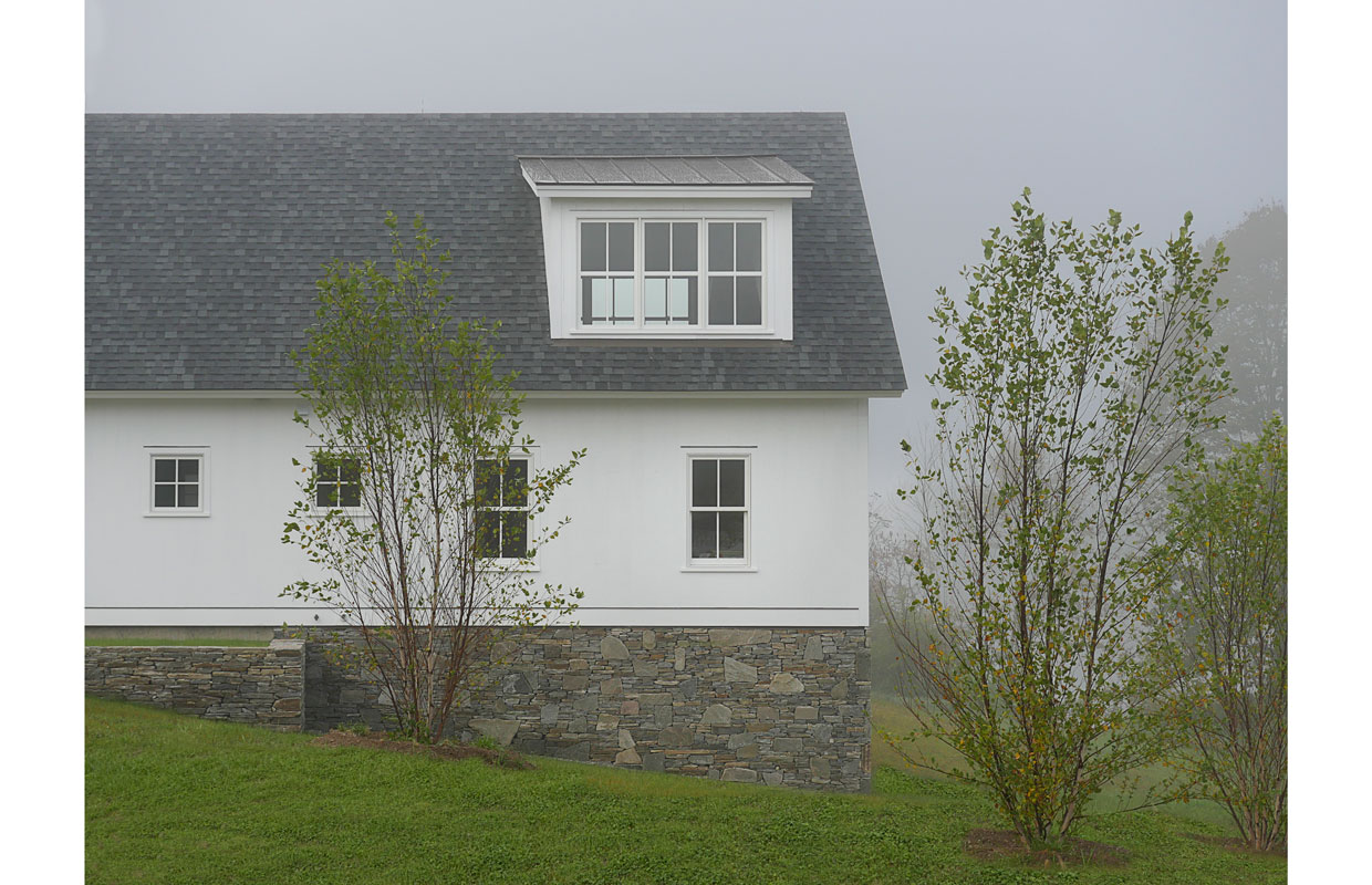 side of a white farmhouse in the fog with a stone foundation