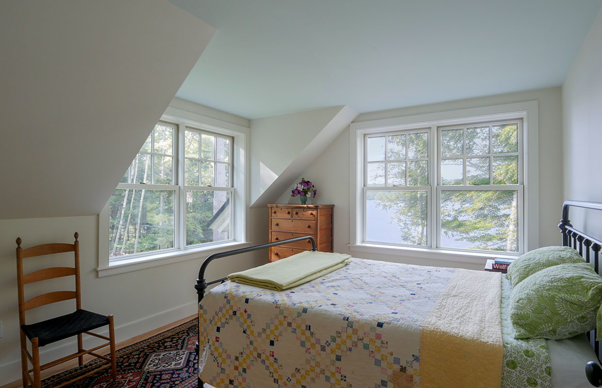 bedroom with slanted ceilings and while walls