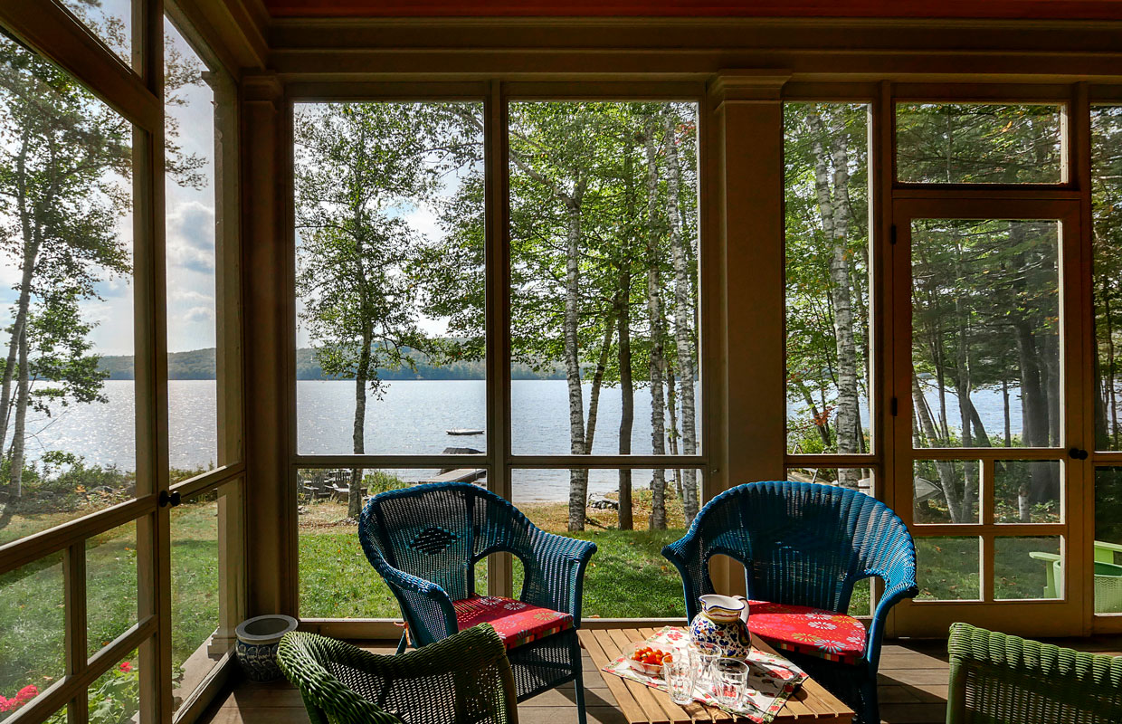 view of a lake from inside a 3 season porch