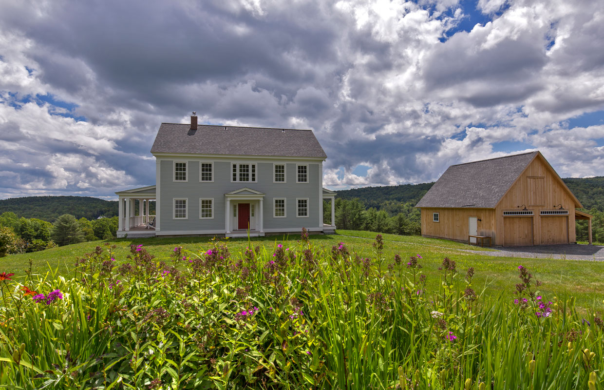 large gray colonial home on a hill with a barn to the right