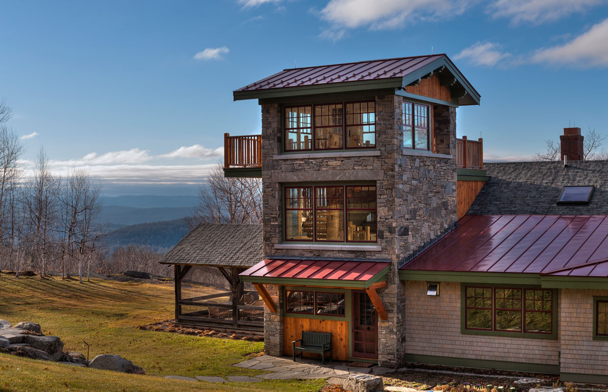 stone tower with a suspended deck on a home with a mountain view in the background
