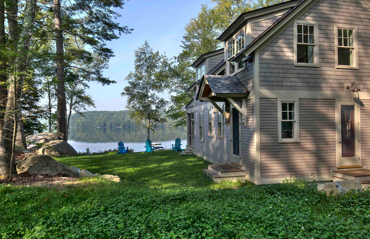 tan house on a lake view from the yard looking at the lake with the house to the right