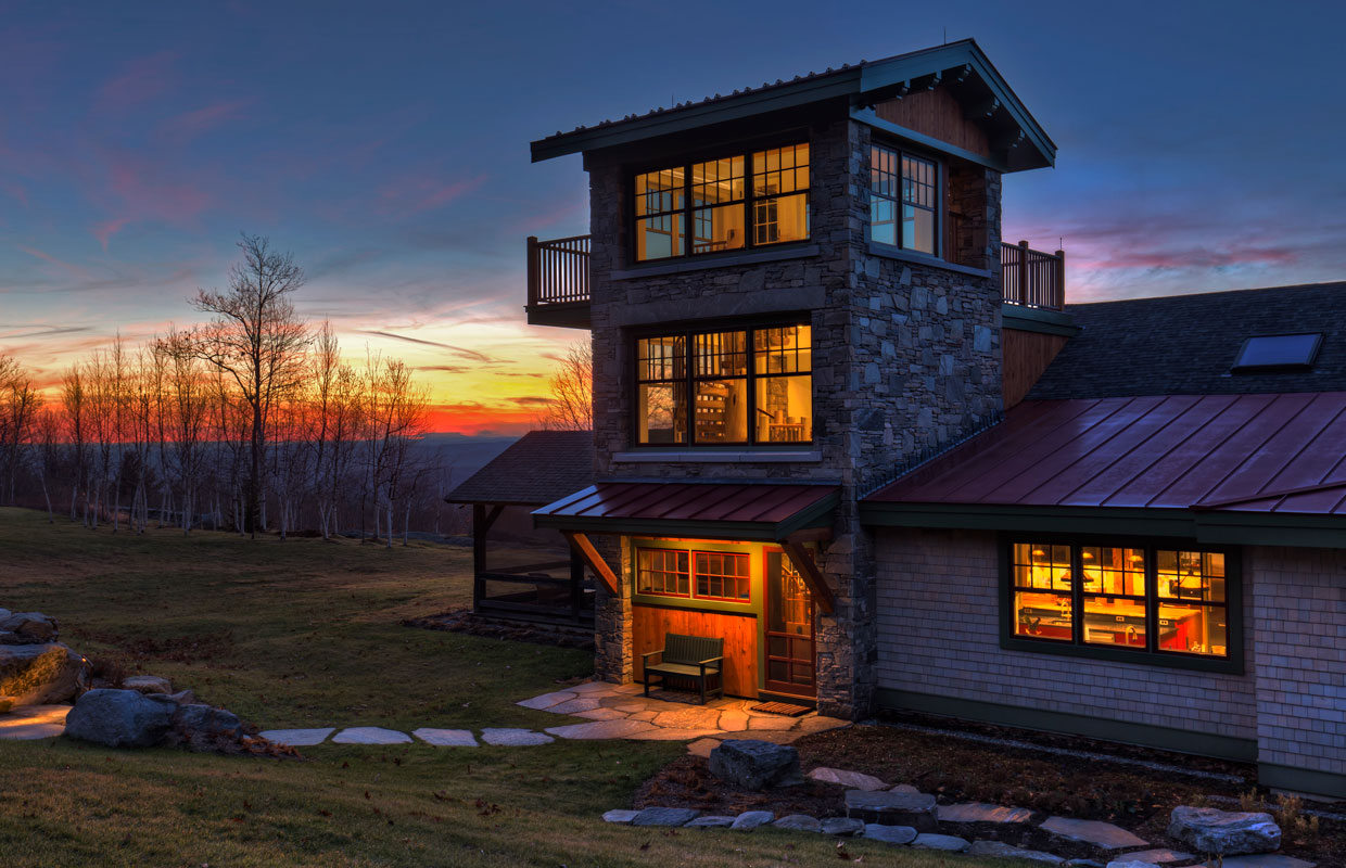 stone tower with a suspended deck on a home with a mountain view in the background at sunset