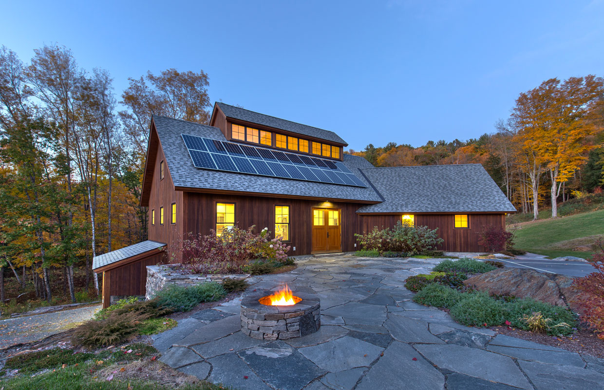 large barn at dusk with solar panels on the roof and a firepit