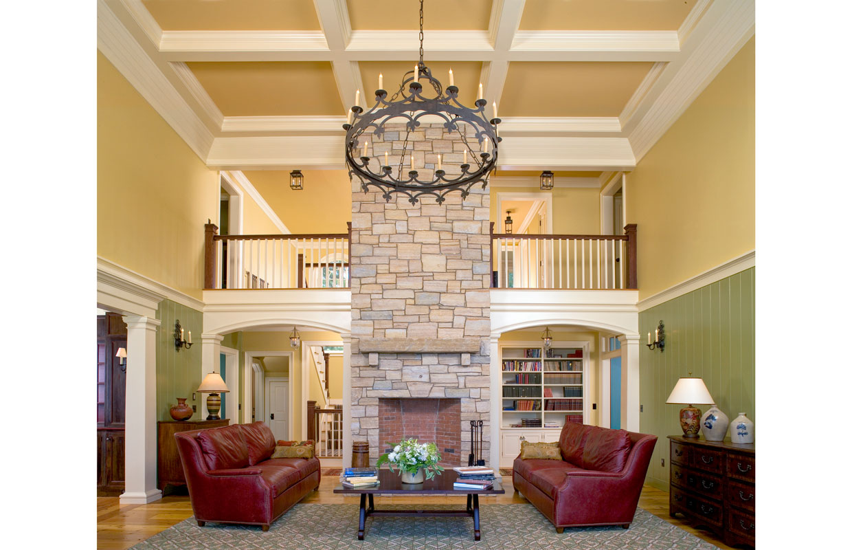 great room with view of a balcony and a large stone fireplace and chimney in the center of the room