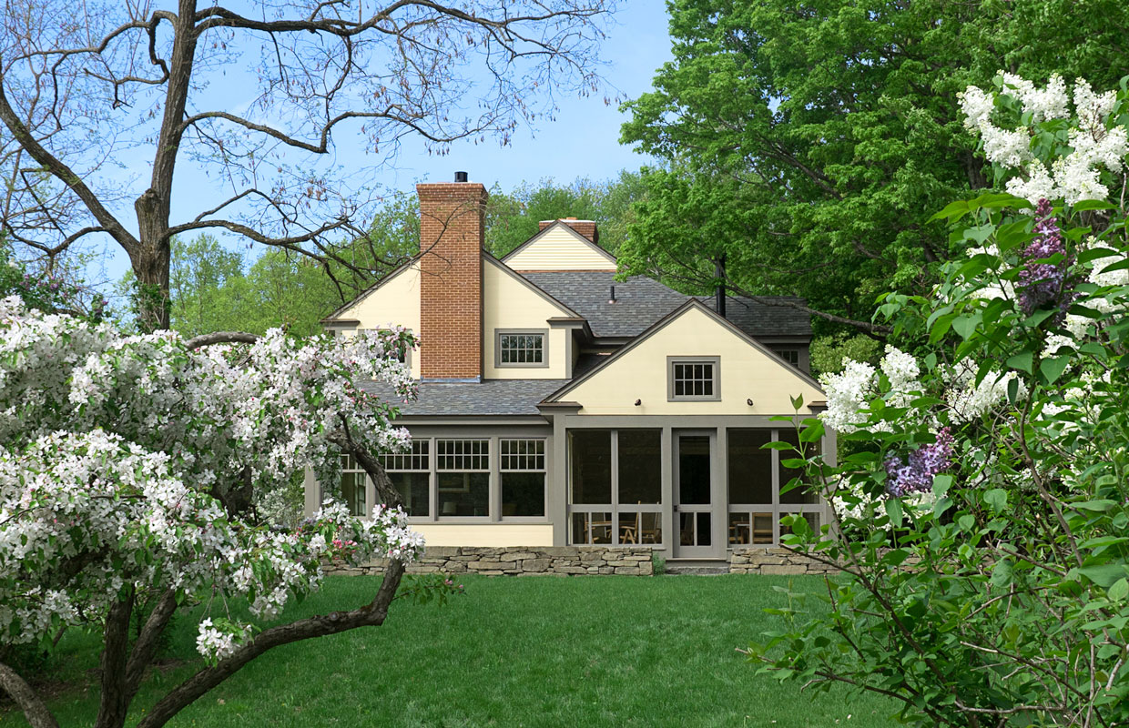 cream house with large windows and blossoming trees in the yard