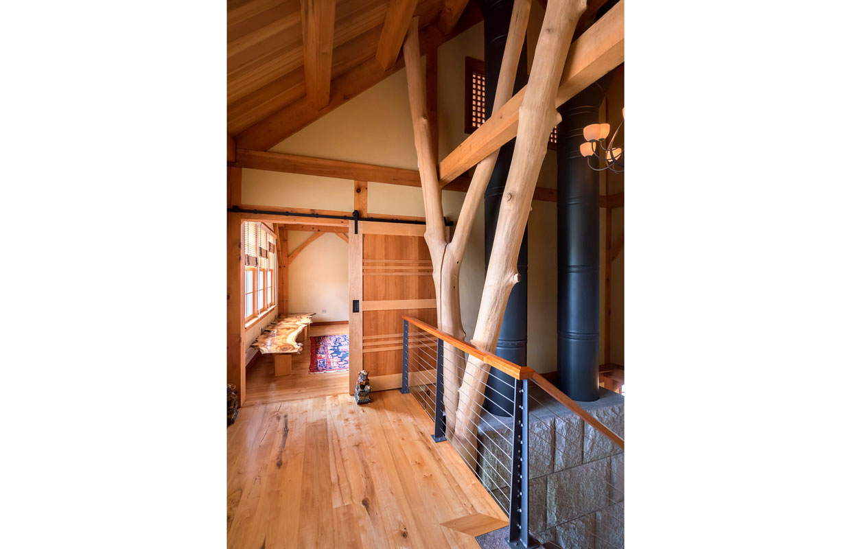 top of a staircase showing a natural tree trunk post and hardwood floors